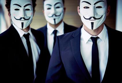 3 Männer in Anzügen mit Guy Fawkes Masken